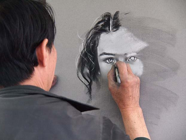 someone drawing a woman's face with chalk